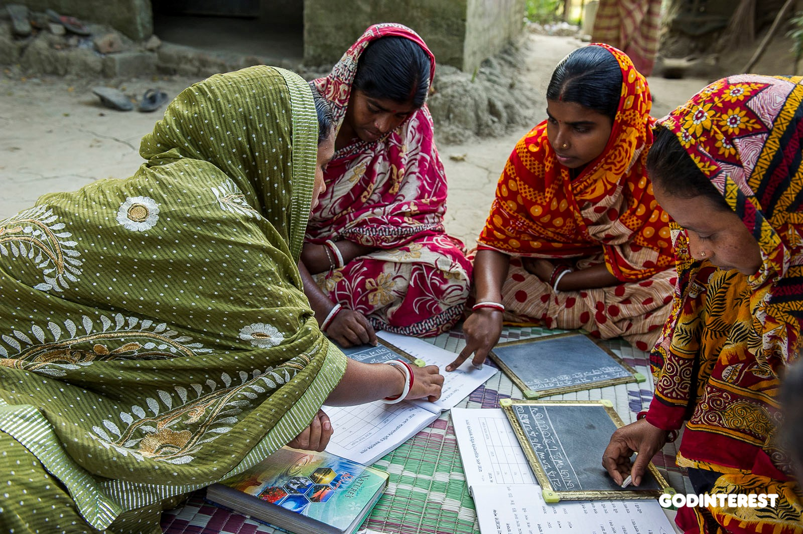 Sarada is teaching three women in a GFA-supported Women's Literacy class.